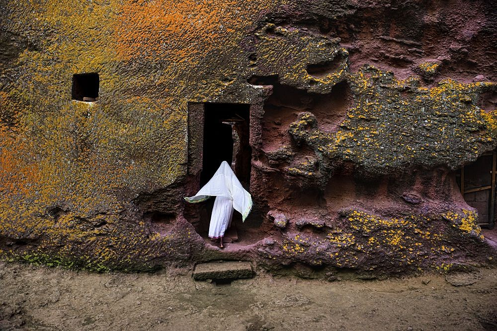 Steve McCurry ,   Woman Enters Medieval Rock-Hewn Church, Ethiopia  ,  2016     FujiFlex Crystal Archive Print ,  30 x 40 in. (Inquire for additional sizes)     ETHIOPIA-10533