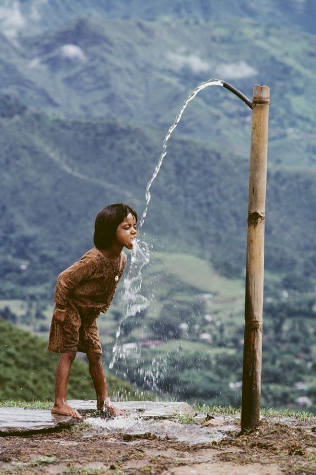 Steve McCurry ,   Child Drinks Water from Well, Nepal  ,  1983     FujiFlex Crystal Archive Print ,  40 x 30 in.     NEPAL-10141